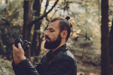 Nature Photography Concepts Professional photographer: stylish bearded man, dressed in a shirt and with a hairdo Top Knot with retro photo camera in hands takes pictures in the woods