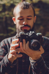 Hipster Travel Lifestyle concept: stylish bearded man, dressed in a shirt and with a hairdo Top Knot with retro photo camera in hands takes pictures in the woods