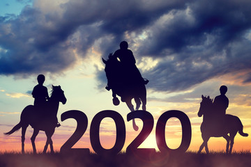 Silhouette of a riders riding a horse in the sunset. Forward to the New Year 2020.