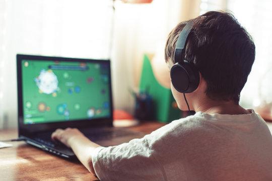 Little dependent gamer boy playing on laptop