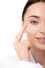 close up of woman applying moisturizing face cream isolated on white