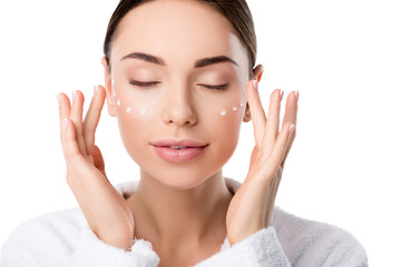beautiful woman with eyes closed applying moisturizing face cream isolated on white