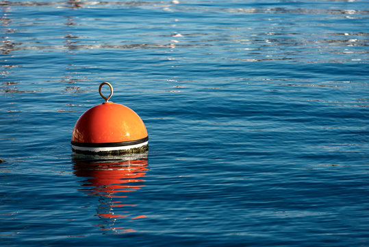 Red and orange mooring buoy in the sea