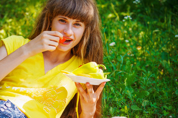 A beautiful young girl with vegetables and fruits lying on the grass on a background of green nature, portrait, close-up, day