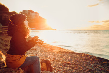 girl photographer is enjoying the beautiful moments of the sunset on the sea coast