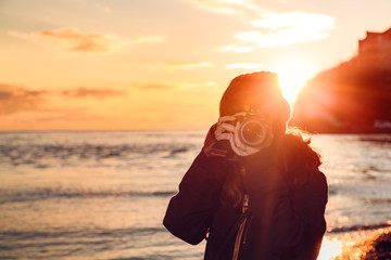 girl photographer catches a beautiful frame of the surrounding nature .on the background of sea sunset