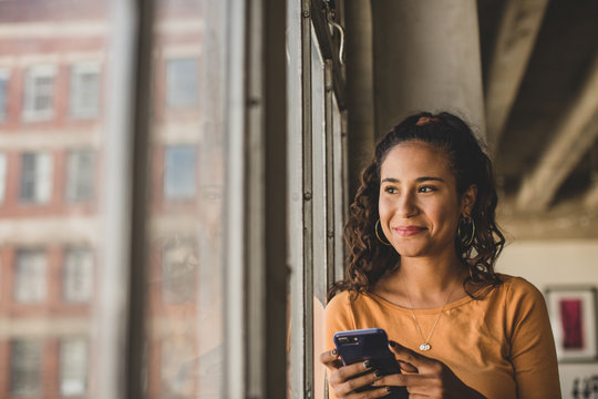 Smiling woman with smartphone looking through window