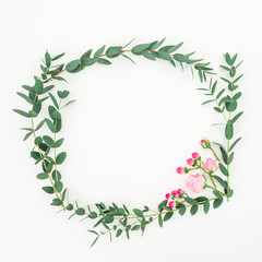 Wreath flower frame of pink roses flowers and eucalyptus branches on white background. Flat lay, top view