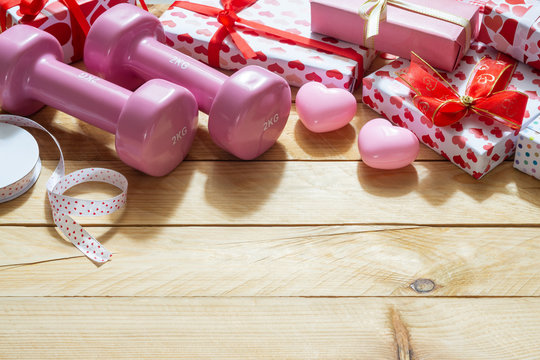 Pink sport dumbbells, heart models and gift boxes on wooden background, Valentines sports background and greeting card any anniversary holiday background concept.