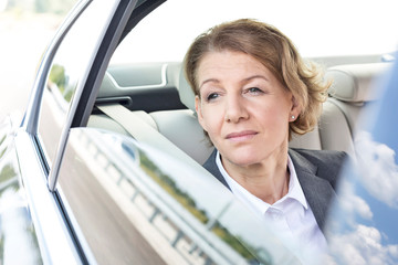 Thoughtful businesswoman looking through window while sitting in car