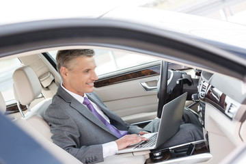 Smiling businessman using laptop while sitting in car