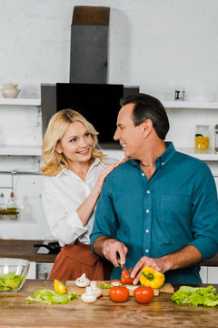 smiling mature wife hugging husband while he cooking salad in kitchen, looking at each other