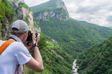 Tourist takes pictures of mountains landscapes with a digital camera