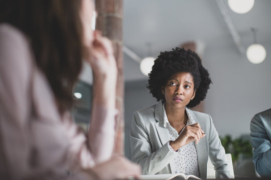 Businesswoman with afro hair listening in meeting
