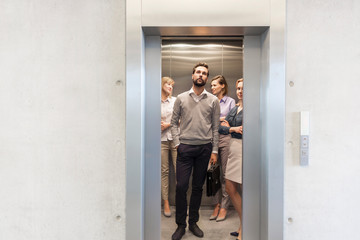 Confident business people standing in elevator at office