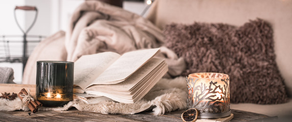 still life home atmosphere in the interior with a book and candles, on the background of cozy bedspreads
