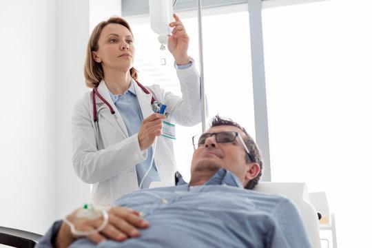 Mature doctor adjusting saline IV drip for patient in hospital ward