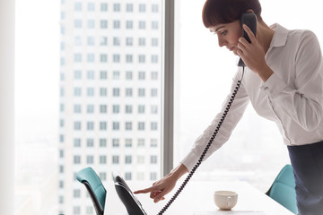 Businesswoman dialing on landline phone at office
