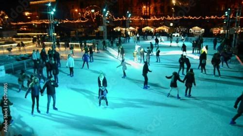 Christmas Ice Skating Rink Decoration.People Skating On The Outdoor Illuminated City Ice Skating
