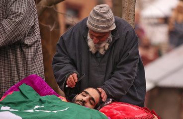 An elderly man combs the hair of Shakoor Ahmad Parray, a suspected militant, who according to local media was killed in a gun battle with Indian security forces, before his funeral in Laribal village