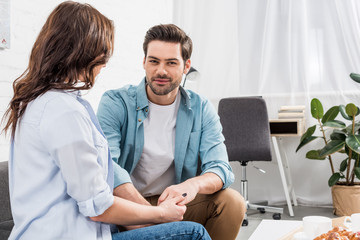 couple sitting on couch and holding hands while man looking at camera at home