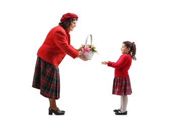 Grandmother giving a basket of flowers to her granddaughter