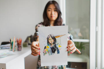 Illustrator showing drawing with self-portrait