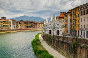 View on  Arno River in Pisa with gothic cathedral Santa Maria della Spina.