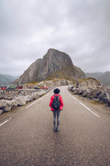 Norway, Lofoten, Hamnoy, back view of man with backpack standing on empty road