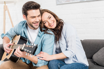 happy couple sitting and embracing on couch while man playing acoustic guitar at home