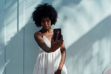Young woman wearing white dress taking a selfie at a wall