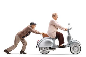 Fototapeta premium Starszy mężczyzna pchanie uśmiechnięta starsza kobieta jedzie na skuterze rocznika