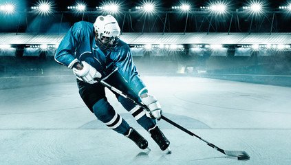 Ice Hockey player athlete in the helmet and gloves on stadium with stick. Action shot. Sport...