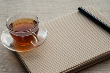 One cup of tea is on the notebook and pen.