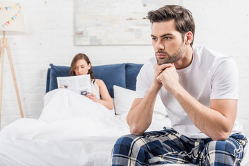 dissatisfied man sitting on bed with folded hands while woman reading newspaper on background