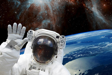 Astronaut in outer space in spacesuit against the background of the earth's blue orbit and space with stars. The elements of this image furnished by NASA