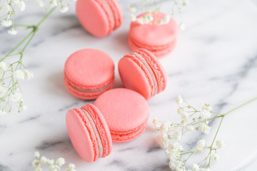 Coral cakes macarons or macaroons on white marble. The concept of Valentines day and spring's celebrating.