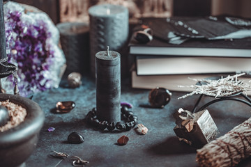 Black candle on a witch's altar for a magical ceremony among crystals and black candles.