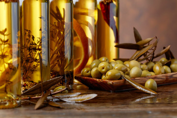 Green olives and bottles of olive oil .