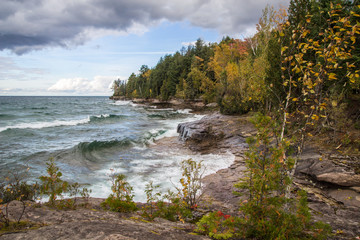 Great Lakes Coastal Landscape. Waves crash on the rocky coast of Lake Superior with fall foliage along the coastal cliffs in Munising, Michigan.