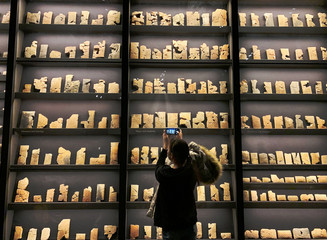 A visitor of the British Museum uses a mobile phone to take a picture of clay tablets from the library collected by King Ashurbanipal, in London