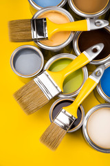 Tin cans with paint and brushes, yellow background