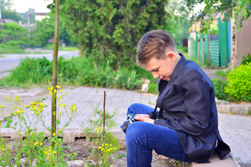 A boy with a camera walks down the street and takes pictures of wild flowers.