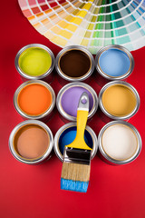 Tin cans with paint and brushes, red background