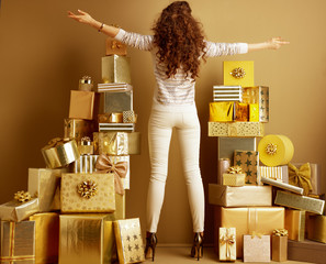 stylish woman among 2 piles of golden gifts rejoicing