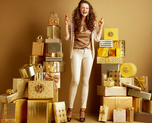 happy fashion-monger with crossed fingers among 2 piles of gifts