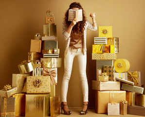 fashion-monger among gifts holding diary in front of face