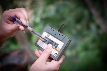 women rewind a cassette tape Vintage compact cassette on blur background, Close up set of old audio tapes, Ret