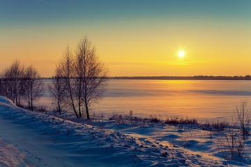 Winter rural landscape at sunrise. Sunrise over the snowy field