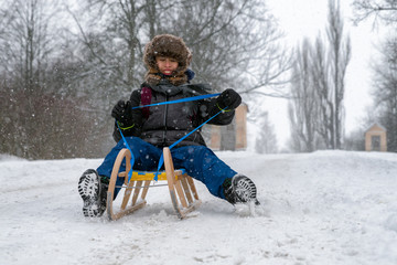 Boy riding a sled